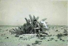 An unidentified member of 7 Para Lt Regt RHA looks into a desert well, Bahrain c 1963.