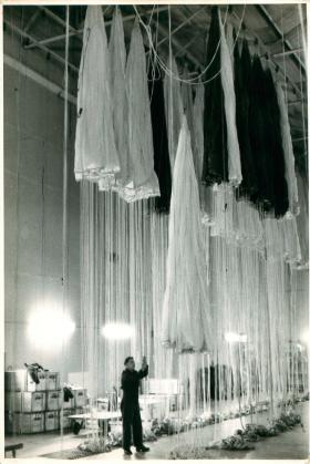 Several white parachutes in the drying hangar at Ringway.