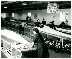 Women packing parachutes on long tables.