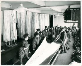 Course students are shown the parachute packing process, Ringway.