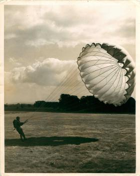 Parachute instructor lands and starts to collapse his parachute, Tatton Park, 1940-1