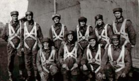 A Parachute course stick photographed during the early parachute training days with their harnesses and headwear on.