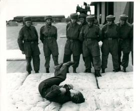 Very early shot of an instructor demonstrating the parachute roll to recruits at Ringway.