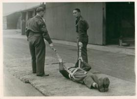 A recruit lies in a harness ready to be pulled in drag training.