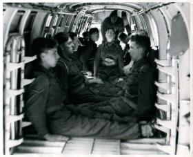 Recruits in a Whitley practise static drills for simulated aircraft exit. One is ready to drop.