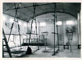 Shot of a parachute training hangar filled with swing harnesses and other equipment.