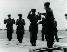 Instructor teaches three recruits the parachute roll on a soft surface.
