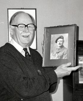 Frank Clarke, with a photograph of himself as a Captain.