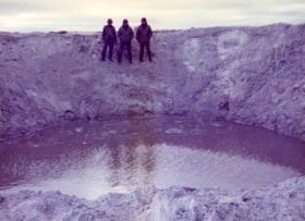 Argentine soldiers pose by a bomb crater, Stanley airfield, Falklands, 1982.