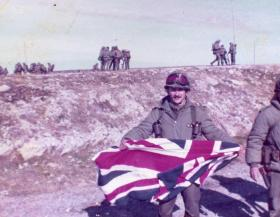 Argentine soldier poses with a Union flag, Stanley airfield, Falklands, 1982.