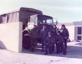 Argentine soldiers pose in front of a captured Royal Marine truck, Falklands, 1982.