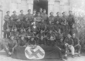 Group photo of 1st Airlanding Brigade Signal Section posing with a captured flag, Italy, October 1943