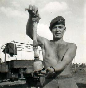 Private Palsen holds a horse leg bone to the camera near Cairo.