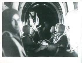 Men sit nervously inside a cramped aircraft waiting to drop, New Delhi, India, 1941.