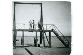 Men standing on wooden swing harness used for teaching parachute control.