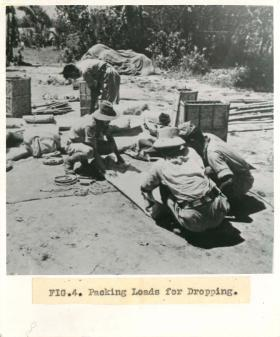 Men from No.1 Indian Air Company squat on the floor outdoors and pack loads for dropping.