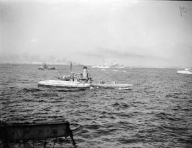 Italian lighters and tugs assist in unloading Royal Navy ships in Taranto Harbour, September 1943.