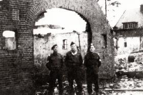 Three men including Sgt 'Johnny' Peters (left) at the 1st Bn, Border Regiment (Airborne) HQ, Oosterbeek 1944.
