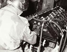 Major Mike Heerey adjusts the portable oxygen console on board an Argosy, 1966