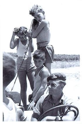 Children listen in on an RT of an Airborne gunner whilst on oil pipeline patrol, Palestine, Spring 1947