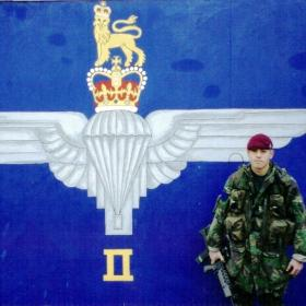 L/Cpl Mark Magreehan with the 2 PARA painting he painted next to the helipad, Crossmaglen, 2003.