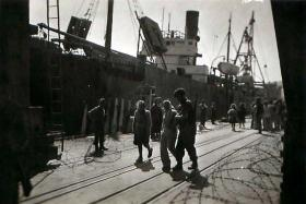 Member of 3rd Parachute Battalion takes illegal immigrant back on board ship at Haifa docks, 1947.