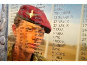 Musician Kate Whittaker reflected in the plaque on the Helmand Memorial Stone at Camp Bastion, Afghanistan 2011