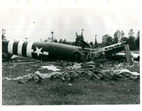 US paratroopers lie dead in France with wreckage of glider in background.