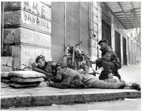 British paratroopers involved in a fire fight on a street corner in Athens, Greece, 1944.