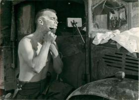 Sergeant Huntly using the mirror of a military vehicle to shave.