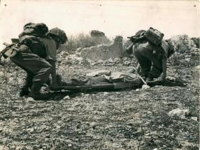 Two RAMC orderlies lifting a man on a stretcher.