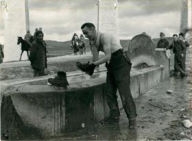 Sergeant Tucker washes his boots in a water trough. Other soldiers and locals look on.
