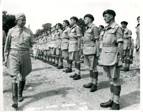 General Eisenhower walks down a line of paratroopers to thank them for their part in Operation Torch.