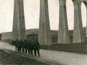 Men of 1st Parachute Squadron RE march under an aqueduct in the Tamera Valley.