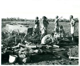 Men from 1st Airlanding Light Regiment RA spread their ammunition on the ground and     discuss the opening range.