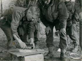 Paratrooper using a glass bottle to crush biscuits to make fishcakes. Others look on.