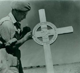 Soldier attends to the field grave of Corporal Page.
