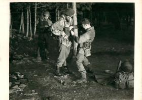Three paratroopers stand in a wooded area at night. One helps the other with his kit.