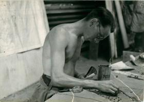 Bare-chested soldier works on Sicily briefing model with aid of aerial photo.