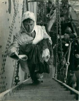 A wounded Lance Corporal Blaycock walks up some ship stairs. He is a survivor of the torpedoed SS Strathallan.