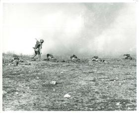 Paratrooper throws a grenade while others take cover on the ground. July, 1943.