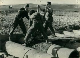 Three men of 1st Parachute Squadron RE preparing a road with concrete.