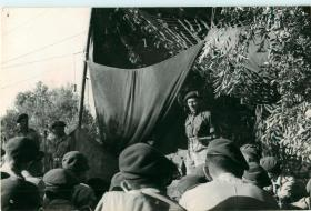 Major General Hopkinson speaking to 21st Independent Parachute Company ffrom a raised platform.