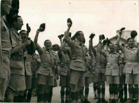 Men of 1st Parachute Brigade raise their berets in the air during General Eisenhower's visit.