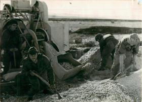Four men of 1st Parachute Squadron RE use shovels to repair a road.