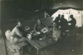 Six men of 1st Airlanding Brigade sit round tables after a meal in their makeshift mess.