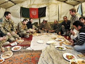 Officers from 3 PARA along with key members of the local community attend a post shura lunch, Afghanistan, 2011