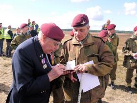 (S/Sgt) Harold Padfield signs a parachute log book, Ginkelse Heide, 22 September 2012.