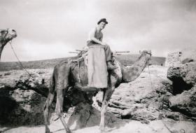 Sigmn Jim Ballantyne on a camel in the Middle East, c1947.