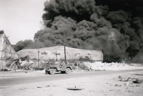 Members of 6th Airborne Divisional Signal Regt survey Oil Depot fire north of Haifa, 1947.